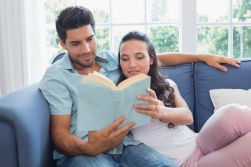 Attractive couple enjoy story book on sofa at home in living room